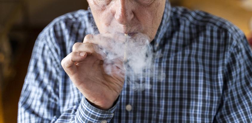 Senior man at home smoking marihuana joint