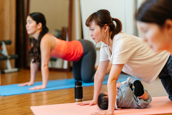 Mother with her baby joining yoga class