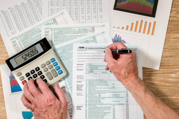 Cropped Hands Of Man Filing Documents Using Calculator At Table