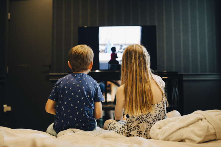 Rear view of siblings watching television while sitting on bed in hotel room