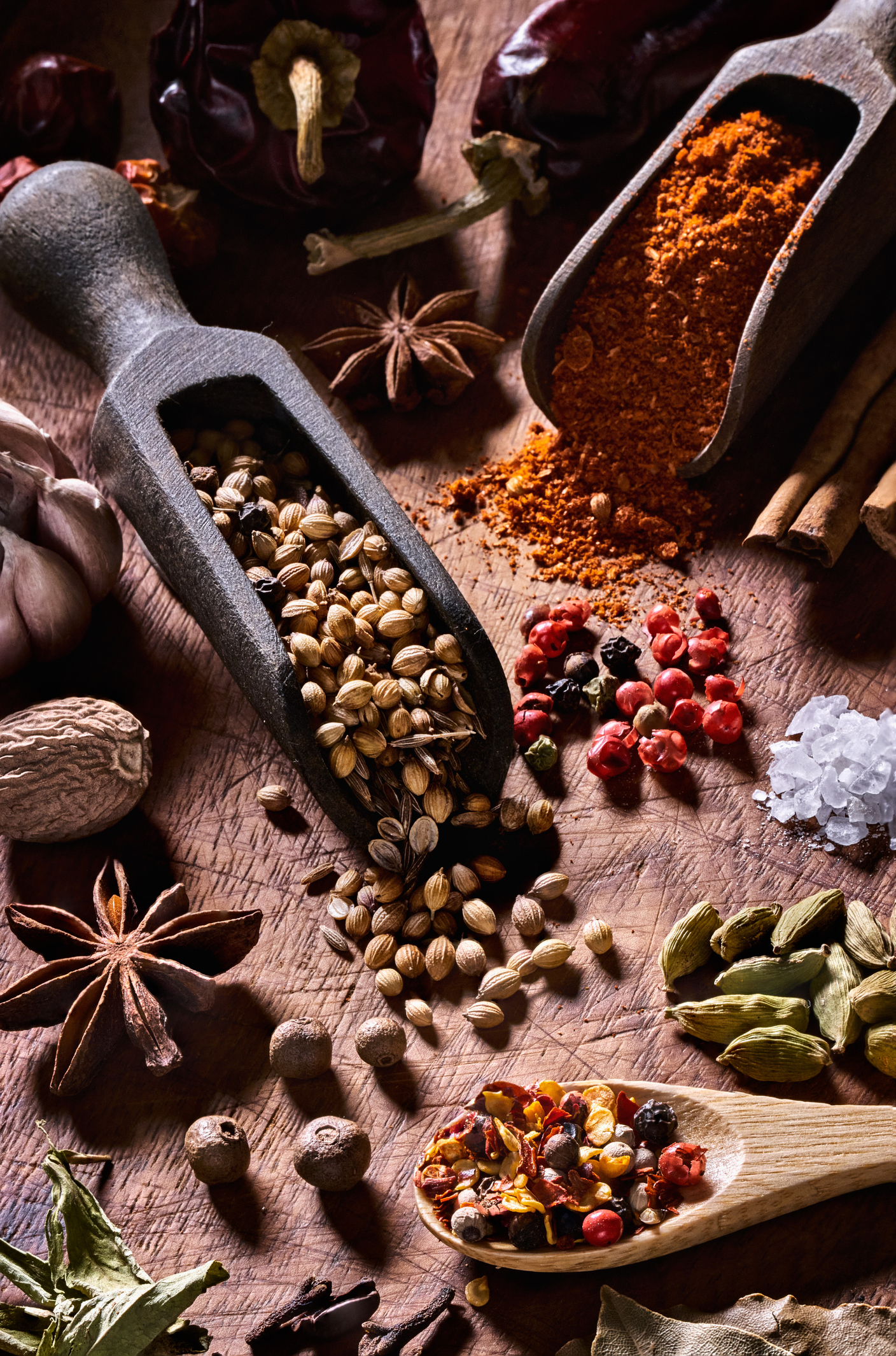 Variety of allspice and herbs on rustic wood table