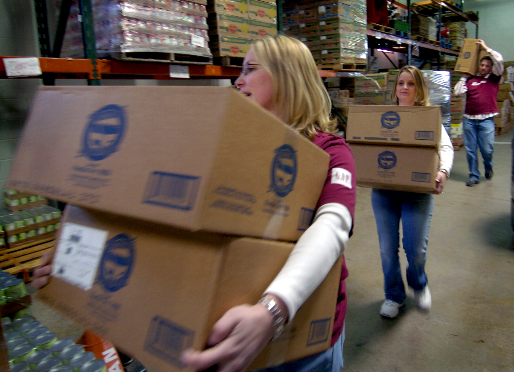 DENVER, COLO. - MARCH 4, 2005 - Patty Colee , front, Chandra Lay , middle, and Patrick Batten , rear, of the Gap, Inc. store at the Park Meadows Shopping Center , three of the store's volunteers at Food Bank of the Rockies in Den