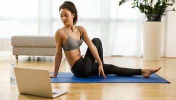 Woman in sportswear practicing yoga and watching tutorial lesson on laptop computer