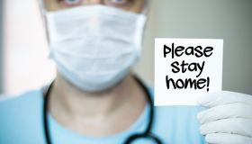 "The middle-aged, green-eyed doctor with a mask on his face and holds a paper that says ""please stay home"""