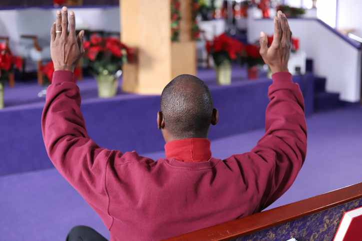 Rear View Of Man Sitting With Arms Raised At Church