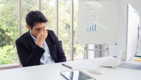 Young Depressed Businessman Sitting At Office