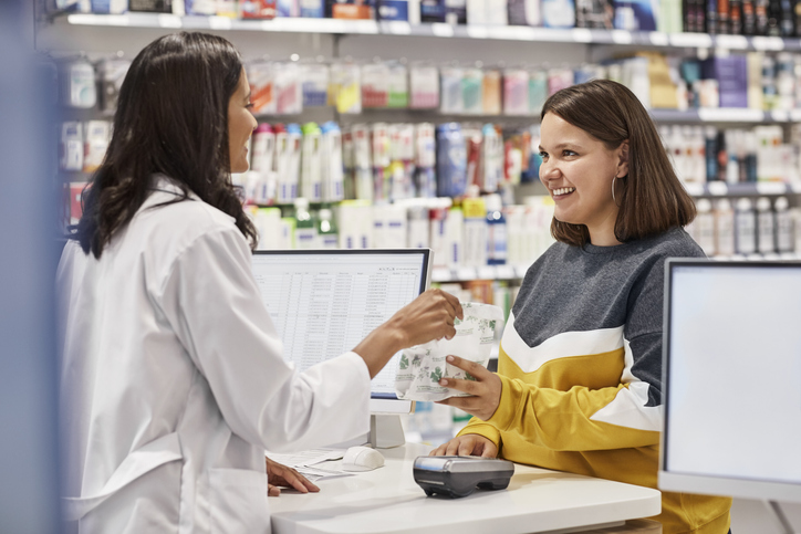 Happy woman taking medicine from cashier