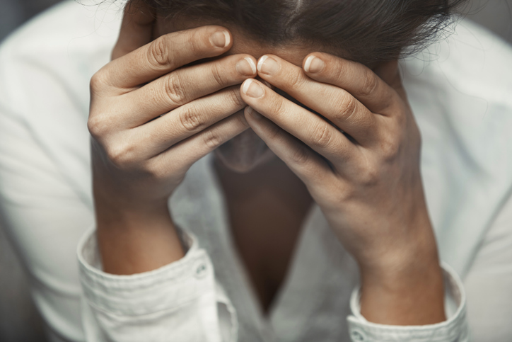 Woman in distress covering her face with hands