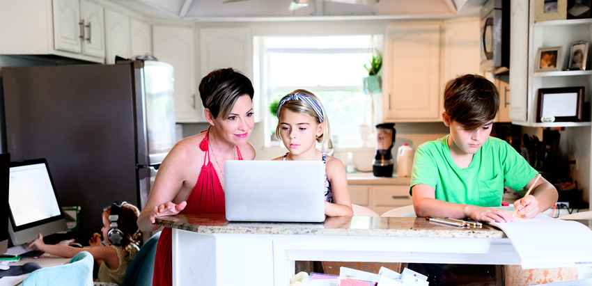 Elementery age children siblings work on schoolwork from home using computer